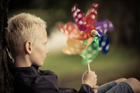 spins: Close up view of blond child holding windmill colored green, blue and yellow as it spins