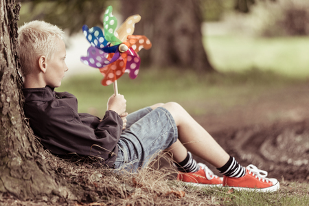 perinola: Blond boy holding colorful whirligig sits by tree while wearing red shoes and blue jean shorts
