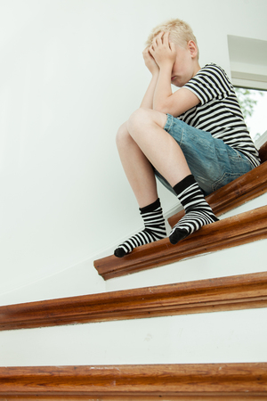 tearful: Blond child crying while seated on stairs and wearing stripped shirt pressing both hands against his face