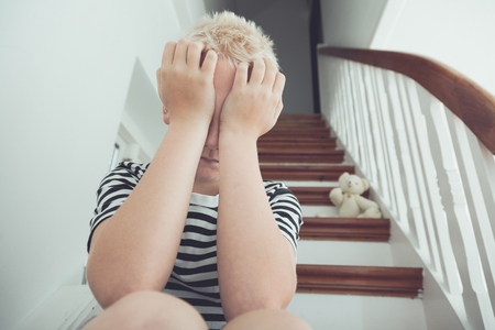 cries: Blond boy pressing hands to face with teddy bear nearby cries while seated on stairs Stock Photo