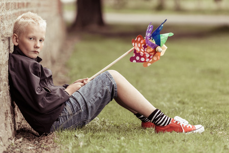 Sad blond boy sits against wall holding whirligig while wearing jean shorts and a black shirt Stock Photo