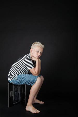 unemotional: Barefoot blond boy wearing stripped shirt stares at camera while sitting on keyboard box