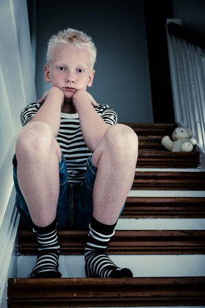 Sad blond boy sits on stairs with elbows on knees beside discarded teddy bear as darkness sets in Stock Photo