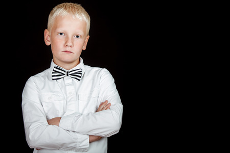 deadpan: blond boy with bad attitude stares at camera with arms crossed against a black background
