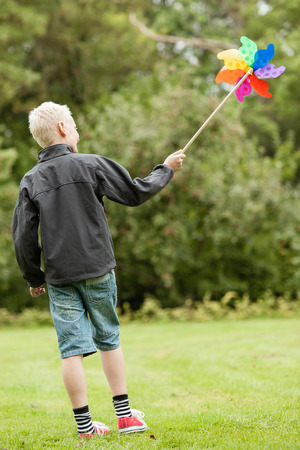 perinola: Boy wearing black jacket holds colorful whirligig while standing in the park on a pleasant afternoon