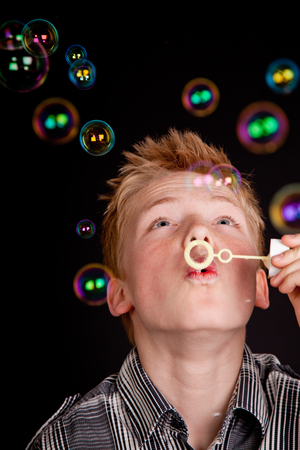 they are watching: Teenage boy having fun blowing soap bubbles looking up watching them as they float above his head with their shiny iridescent colors on a black background
