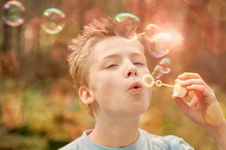 spiked hair: Single blond boy with spiked hair and gray shirt holding plastic wand blowing bubbles outdoors