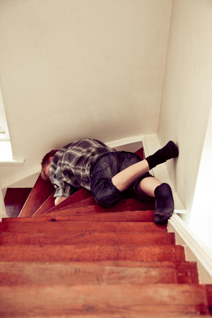 blacked: Young boy lying sprawled face down and motionless on a staircase in a house conceptual of an accident drunkenness or drug abuse Stock Photo