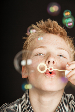 Single handsome boy over black background blowing bubbles through small section on plastic wand Stock Photo