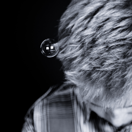 downcast: Black and white top down view on bubble attached to hair of unidentifiable boy looking downward over black background