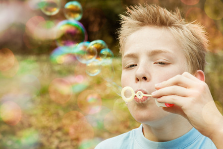 spiked hair: Cute blond male child with spiked hair and blue shirt holding plastic wand blowing bubbles outdoors. Includes copy space. Stock Photo