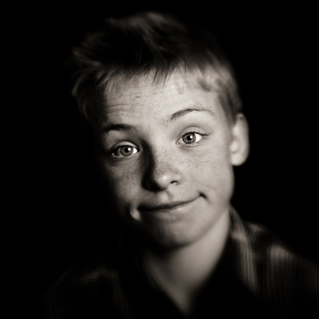 incertitude: Cute young boy with a whimsical wry expression looking with wide eyed perplexity at the camera, square monochrome portrait