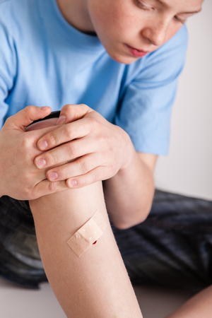eyes downcast: Single young boy in blue shirt and dark pants holding knee with bandage covering wound on shin Stock Photo
