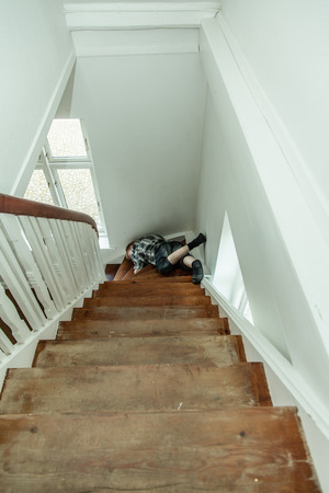 tripped: View from the top looking down at a motionless injured boy lying sprawled on the stairs on the landing having missed his footing and taken a fall