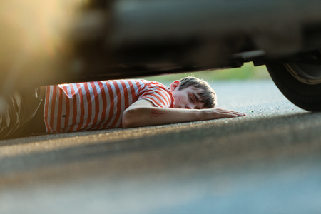 sprawled: Hurt and unconscious male child in red and white striped shirt sprawled out on asphalt underneath automobile
