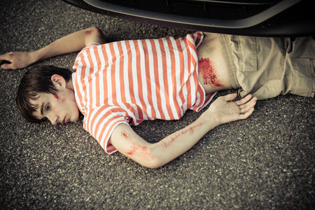 bloodied: Dead child hurt in a car accident laying down on ground with bloodied back, arms and head with bumper over him