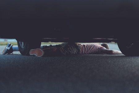 reckless: Unconscious child stuck underneath car with copy space at top and bottom for concept about reckless driving