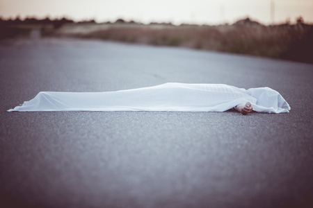 mva: Dead body with hand sticking out from under white sheet in middle of road with copy space