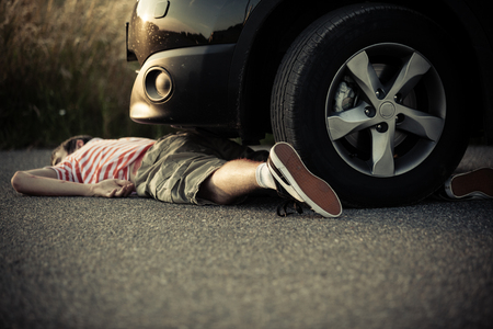 Dead child in shorts and striped shirt laying on street in front of car with copy space on asphalt