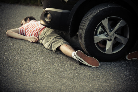 mva: Car tire and bumper over single unconscious boy laying down on street with severe injuries Stock Photo