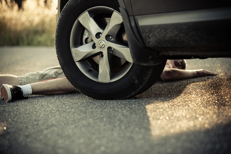 mva: Car wheel close to injured child in shorts on street for theme about dangerous car accidents Stock Photo