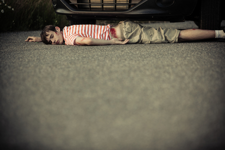 bloodied: Child with bloodied hip, striped red and white shirt and shorts on ground near front of car. Includes copy space.