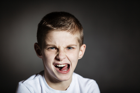 glowering: Solitary boy wearing white shirt making faces against black background