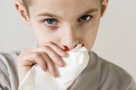 One serious male child wearing dull colored shirt uses tissue to stop bleeding nose against a grey background