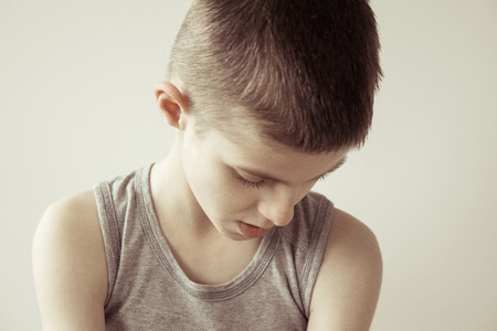 contemplative: Contemplative brown haired boy in gray sleeveless shirt against a dull background