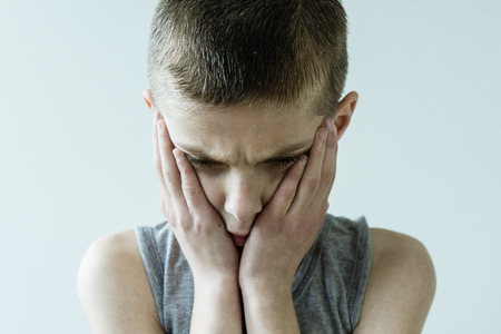 sadly: Head and Shoulders Close Up of Troubled Young Boy Wearing Grey Tank Top Looking Down Sadly and Holding Face in Hands in Studio with Light Colored Background