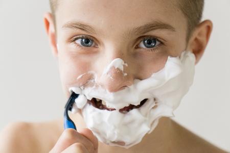 頭と肩は、白い背景とスタジオでプラスチック製のカミソリとシェービング クリームのシェービングで覆われた顔でカメラに笑顔興奮した若い少年 写真素材