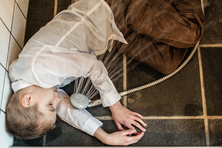 passed out: Overhead view of fully clothed boy passed out in tiled bathroom next to running water