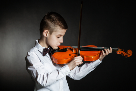 absorbed: Young solo musician holds violin under his chin poised to play in a darkened room