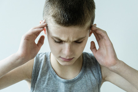 perturbed: Head and Shoulders Close Up of Stressed Young Boy Wearing Grey Tank Top Looking Down in Pain and Holding Temples with Hands in Studio with White Background Stock Photo