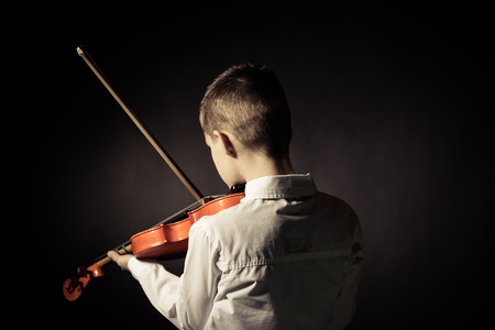 Rear view of male child with short brown hair playing violin in darkened room Standard-Bild