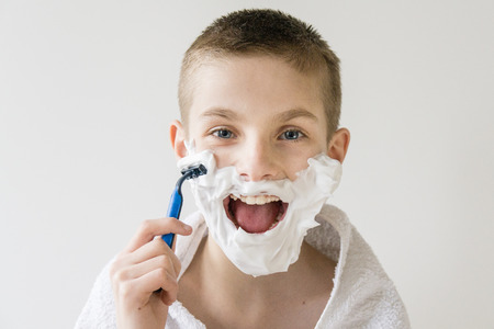 hilarity: Head and Shoulders Portrait of Excited Young Boy with Open Mouth and Face Covered with Shaving Cream Shaving with Plastic Disposable Razor - Playing Grown Up in Studio with White Background
