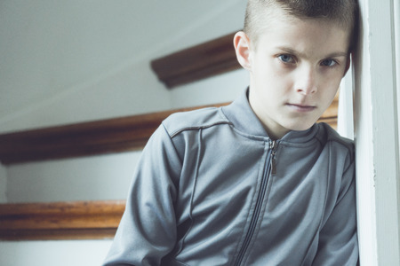 introspective: Serious lonely boy with brown hair in gray jacket leans against white door frame beside wooden staircase
