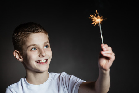 Amazed brown haired boy with blue eyes in white shirt holding lit sparkler Stock Photo
