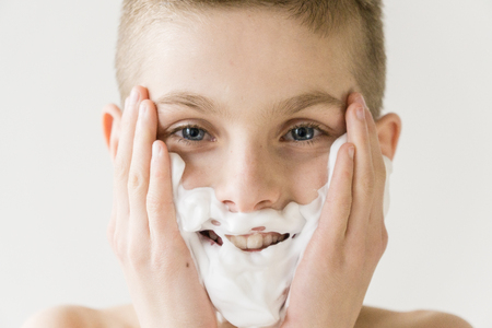 grown up: Close Up Head and Shoulders Portrait of Smiling Young Boy Applying Shaving Cream to Face in Studio with White Background - Boy Playing Grown Up and Looking Happy