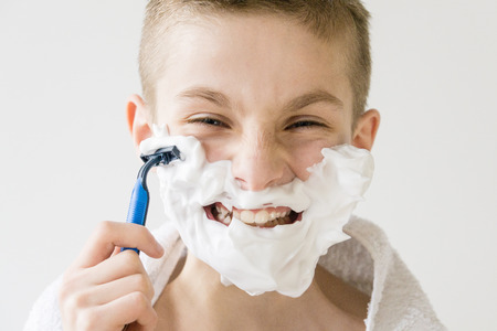 impish: Head and Shoulders Close Up of Excited Young Boy Playing Grown Up - Smiling Boy Shaving Face with Plastic Razor and Squinting at Camera in Studio with White Background Stock Photo
