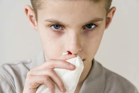 Boy in grey shirt with brown hair and blue eyes holds tissue to bloody nose against a dull background
