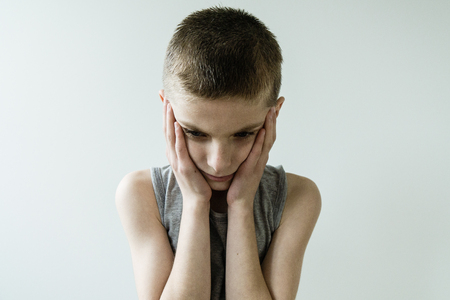 dispirited: Waist Up of Troubled Young Boy Wearing Grey Tank Top and Holding Head in Hands While Looking Down Sadly in Studio with Light Colored Background with Copy Space