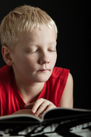 downcast: Close up on cute single blond boy with serious expression in red shirt reading book