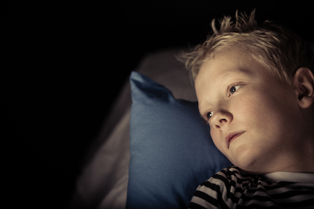 unemotional: Sleepless little blond boy staring out past black background with copy space while laying on pillow