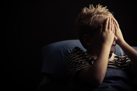 Single little boy covering eyes while laying in bed with dark background. Includes copy space.