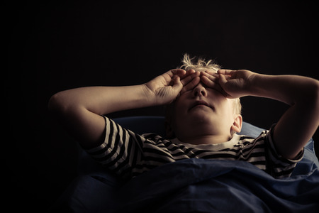 Single male child rubbing eyes while laying in bed