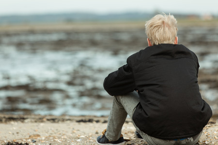 Rear view of blond person in black jacket and gray jeans sitting on rocky beach during low tide