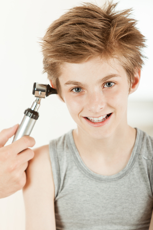 Portrait of smiling young boy having his ear test by pediatric otolaryngology doctor