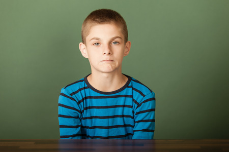 sombre: Young boy with short hair sadly looking at camera wearing blue t-shirt sitting at desk over green chalkboard background Stock Photo