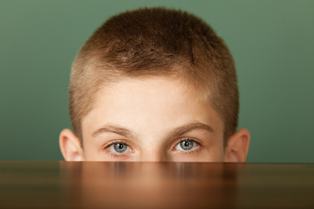 earnest: Close-up of young boy with short haircut peeping out the table with his emotionless eyes, against green chalkboard background